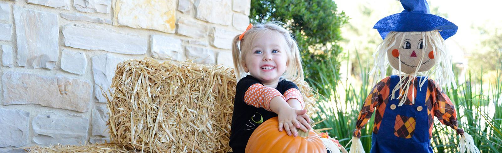 Rancho Sienna Girl Holding Pumpkin with Dog and Scarecrow at Harvest Festival Event